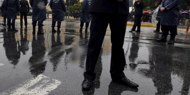 Policemen stand guard in front of a crowd of Greeks watching a military parade during Independence Day celebrations in Athens, March 25, 2015. Thousands of Greeks braved heavy rainfall on Wednesday to watch the Independence Day parade in front of the parliament after being banned in previous years for security reasons. REUTERS/Yannis Behrakis