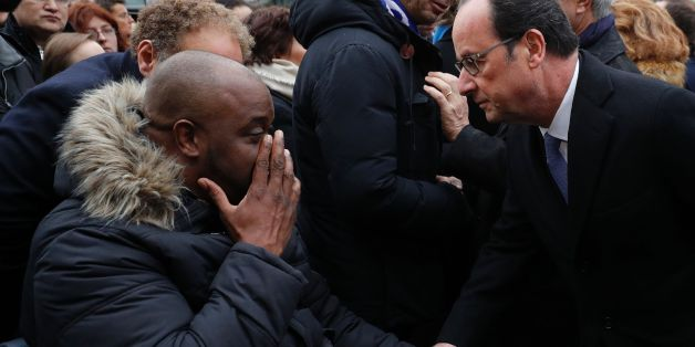 French President Francois Hollande (R) speaks with a victim after unveiling a commemorative plaque outside the Stade de France stadium, in Saint-Denis, north of Paris, on November 13, 2016, during a ceremony to mark the first anniversary of the Paris terror attacks.