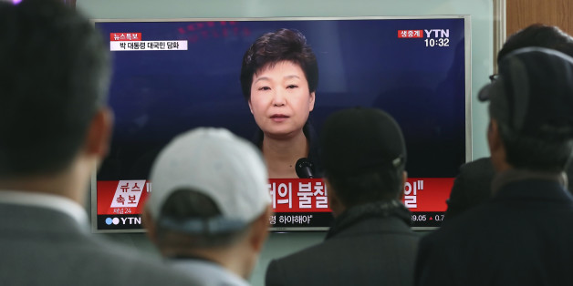 "FILE - In this Friday, Nov. 4, 2016 file photo, people watch a TV screen showing the live broadcast of South Korean President Park Geun-hye's address to the nation on a ""heartbreaking"" scandal, at the Seoul Railway Station in Seoul. South Korean prosecutors are likely to question Park over suspicion that she let a shadowy longtime confidante manipulate power from behind the scenes, state-run Yonhap news agency reported Sunday, Nov. 13. (AP Photo/Lee Jin-man, File)"