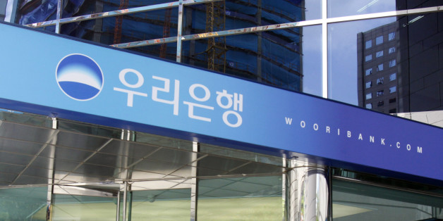 People walk into the headquarters of Woori Bank in Seoul July 20, 2010. South Korea will announce plans next week to sell a 57 percent stake in Woori Financial Holdings Group that may fetch more than $6 billion, a senior official familiar with the matter said. Picture taken on July 20, 2010.  REUTERS/Truth Leem (SOUTH KOREA - Tags: BUSINESS)