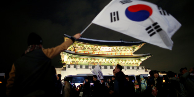A man waves a national flag as people march toward the Presidential Blue House during a rally demanding President Park Geun-hye to step down in central Seoul, South Korea, November 12, 2016.   REUTERS/Kim Hong-Ji