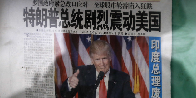 """A man is reflected on a glass as he reads a Chinese newspaper with a photo of U.S. President-elect Donald Trump, displayed on a newspaper board in Beijing, Thursday, Nov. 10, 2016. Donald Trump's promise to put America first helped propel him to the U.S. presidency. But he also unleashed uncertainty on the global economy by skewering trading partners and offering few specifics that might calm allies or businesses. The headline reads """"President Donald Trump delivers a mighty shock to America.""""  (AP Photo/Andy Wong)"""