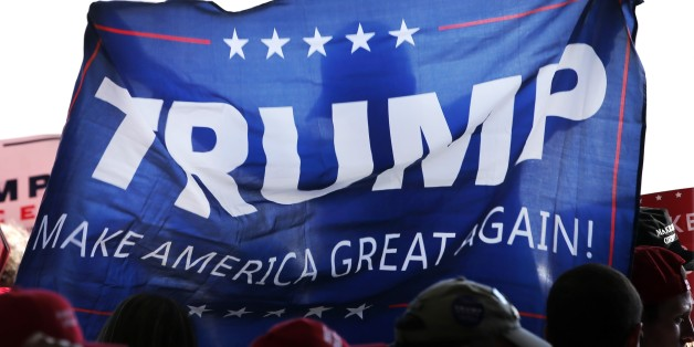 A supporter of Republican presidential candidate Donald Trump, holds up a campaign flag before Trump's arrival at a campaign stop at the Minneapolis International Airport Sunday, Nov. 6, 2016, in Minneapolis . (AP Photo/Charles Rex Arbogast)