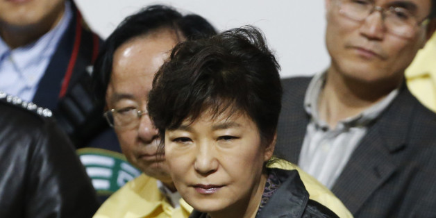 """South Korean President Park Geun-hye (C) listens to a family member of a missing passenger who was on South Korean ferry """"Sewol"""", which sank at the sea off Jindo, during her visit to a gym where family members gathered, in Jindo April 17, 2014. Rescuers fought rising winds, strong waves and murky waters on Thursday as they searched for hundreds of people, mostly teenage schoolchildren, still missing after a South Korean ferry capsized more than 24 hours ago.   REUTERS/Kim Hong-Ji (SOUTH KOREA -"""