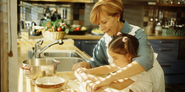Grandmother helping granddaughter roll out pastry