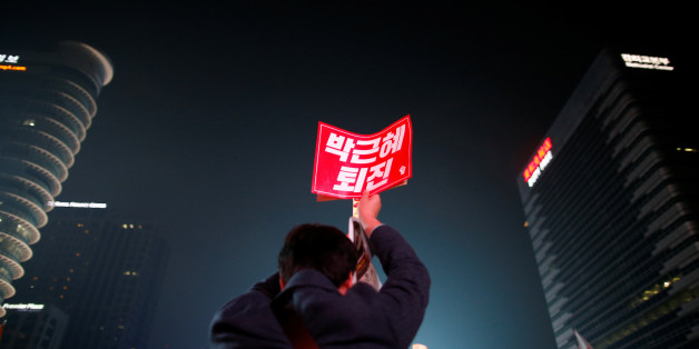 """A man holds up a placard that reads """"Call for Park Geun-hye to step down"""" during a rally calling on embattled President Park Geun-hye to resign over a growing influence-peddling scandal, in central Seoul, South Korea, November 5, 2016. REUTERS/Kim Hong-Ji"""