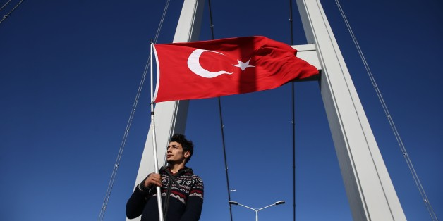 ISTANBUL, TURKEY - NOVEMBER 13: A man raises Turkish flag as Athletes and thousands of people take part in the 38th Vodafone Istanbul Marathon, the worlds only road race where people can run from Asia to Europe, at the July 15 Martyrs Bridge in Istanbul, Turkey on November 13, 2016. The 38th Vodafone Istanbul Marathons campaign for this year is: We are running for the July 15 martyrs. The races started on the Asian side of the July 15 Martyrs Bridge, formerly known as the Bosphorus Bridge, and w