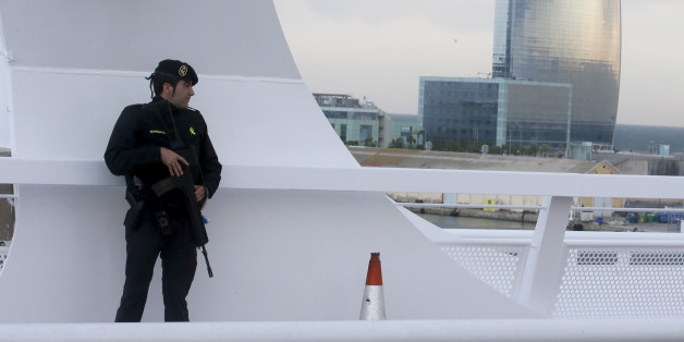 """A civil guard keeps watch while restricting public access on a bridge which leads to the cruise ship docks of Barcelona port, where cruise ship MSC Splendida has docked after leaving Tunis March 20, 2015.  Tunisia said it would deploy the army to major cities and arrested nine people on Thursday after 20 foreign tourists, of which 12 were passengers of MSC Splendida, were shot dead in an attack on a museum which Islamic State militants called """"the first drop of the rain"""".  REUTERS/Albert Gea"""