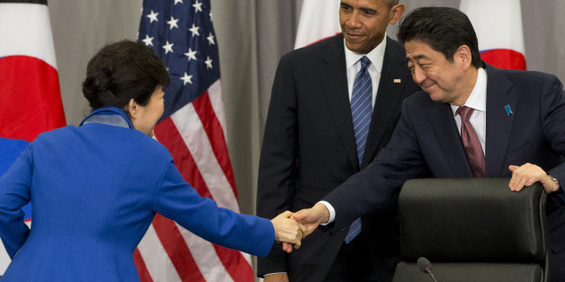 South Korean President Park Geun-hye, left, shakes hands with Japanese Prime Minister Shinzo Abe, right, as President Barack Obama watches, after their meeting at the Nuclear Security Summit in Washington, Thursday, March 31, 2016. (AP Photo/Jacquelyn Martin)