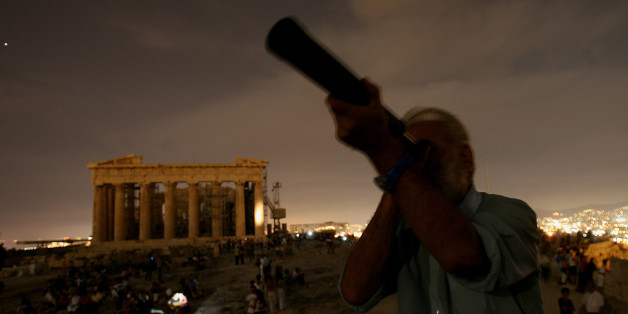 A Greek  man looks through his telescope at the full moon as at the backround is seen the ancient temple of Parthenon at Acropolis hill, in Athens on Wednesday, Aug. 9, 2006. Many archaeological sites in Greece were open for the public Wednesday night for the full moon. (AP Photo/Petros Giannakouris)