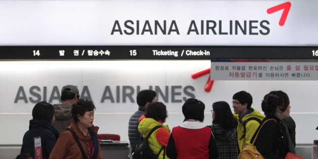 Passengers wait to buy tickets at the Asiana Airlines ticketing counter at Gimpo airport in Seoul, South Korea, Friday, Nov. 8, 2013. Asiana Airlines Inc. reported its first profitable quarter this year as travel peaked during the fall holidays.(AP Photo/Ahn Young-joon)