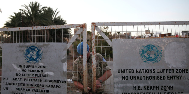 A U.N. soldier locks a gate inside the UN-controlled buffer zone in Nicosia, Cyprus November 7, 2016. REUTERS/Yiannis Kourtoglou