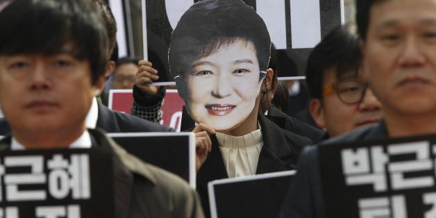 """A South Korean protester wearing a mask of South Korean President Park Geun-hye marches during a rally calling for Park to step down in Seoul, South Korea, Friday, Nov. 18, 2016. South Korea's parliament on Thursday passed a law that would allow a special prosecutor to investigate a corruption scandal threatening the presidency of Park. The cards read """"Park Geun-hye should step down."""" (AP Photo/Ahn Young-joon)"""