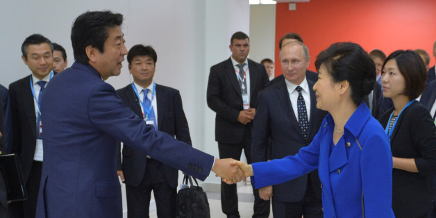 Japanese Prime Minister Shinzo Abe (L) shakes hands with South Korean President Park Geun-hye as Russian President Vladimir Putin stands in the background during the Eastern Economic Forum in Vladivostok, Russia, September 3, 2016. Sputnik/Kremlin/Alexei Druzhinin/via REUTERS  ATTENTION EDITORS - THIS IMAGE WAS PROVIDED BY A THIRD PARTY. EDITORIAL USE ONLY.