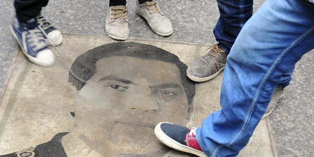 Protestors step on a carpet depicting ousted Tunisian President Zine El Abidine Ben Ali during a demonstration to mark the third anniversary of his departure, Tuesday, Jan. 14, 2014. Three years ago, mass public protests ousted Tunisian President Zine el-Abidine Ben Ali from office. (AP Photo/Hassene Dridi)
