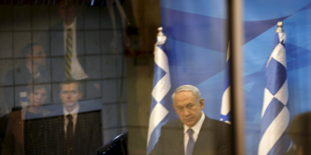 A reflection of Israeli Prime Minister Benjamin Netanyahu (C) is seen as he delivers a joint statement with his Greek counterpart Alexis Tsipras in Jerusalem, November 25, 2015. REUTERS/Ronen Zvulun