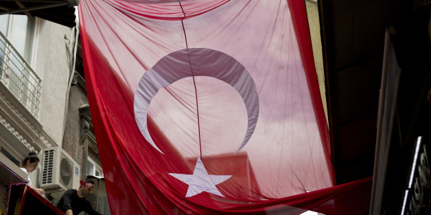 A man tries to unwrap a giant Turkish flag at Grand bazaar, one of the largest and oldest covered markets in the world, in Istanbul, Monday, July 18, 2016. The European Union and the United States expressed alarm Monday with Turkey's response to a failed coup, telling the NATO member and EU aspirant that it must uphold democracy and human rights as it pursues the military officers and anyone else involved in the plot. (AP Photo/Petros Giannakouris)