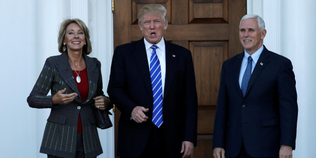 U.S. President-elect Donald Trump (C) and Vice President-elect Mike Pence stand with Betsy DeVos (L) before their meeting at the main clubhouse at Trump National Golf Club in Bedminster, New Jersey, U.S., November 19, 2016.  REUTERS/Mike Segar