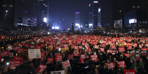 """South Korean protesters hold up candles and placards during a rally calling for South Korean President Park Geun-hye to step down in Seoul, South Korea, Saturday, Nov. 19, 2016. For the fourth straight Saturday, masses of South Koreans filled major avenues in downtown Seoul demanding an end to the presidency of Park, who prosecutors plan to question soon over an explosive political scandal. The letters read """"Park Geun-hye, Step Down."""" (AP Photo/Lee Jin-man)"""