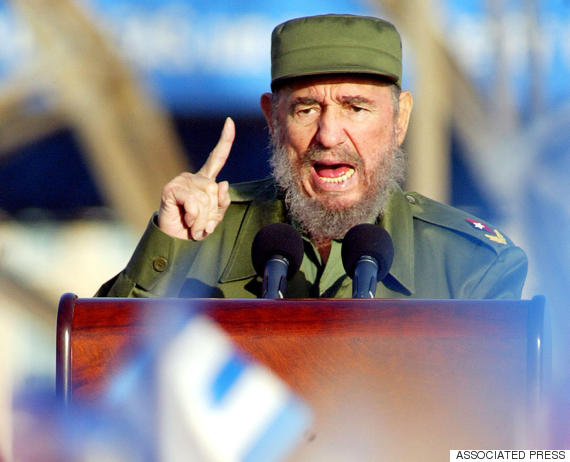 fidel castro gestures as people wave flags