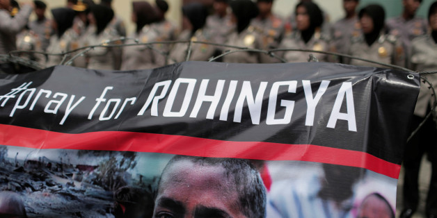 A banner is seen during a protest against what demonstrators say is the crackdown on ethnic Rohingya Muslims in Myanmar, as police stand guard in front of the Myanmar embassy in Jakarta, Indonesia November 25, 2016. REUTERS/Beawiharta