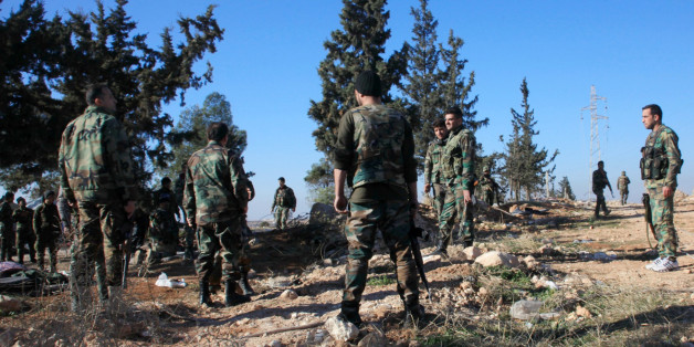 Syrian government forces inspect an area near the village of Khan Tuman, south from the provincial capital Aleppo, on December 22, 2015, two days after army units and other pro-regime forces recaptured several areas in the north of the country from Islamist forces, including Al-Qaeda's Syrian branch, Al-Nusra Front and Ahrar al-Sham brigade. Khan Tuman was the scene of fierce clashes between loyalist forces, including fighters of Lebanon's Shiite militia Hezbollah, and Islamist rebels, said the