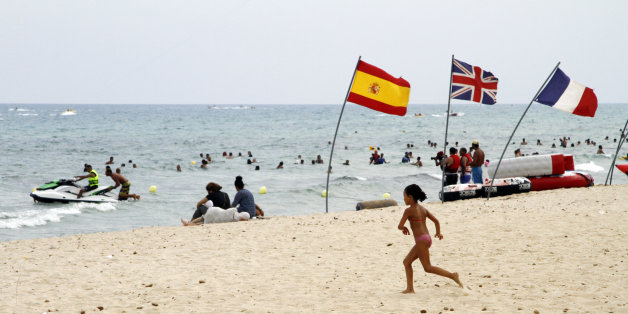 In this Aug. 9, 2015 photo, a young girl runs past European flags on a crowded beach in Hammamet, Tunisia.  The jet skis roar by the shore and the water is full of splashing children along the Tunisian Riviera, where despite the deadly attack that killed 38 tourists in June, the beaches are still full _ for now. Europeans have abandoned this North African country, leaving just local Tunisian beach-goers and visiting Algerians. But they will be gone by month's end, and then the real pain for the country's all-important tourism industry will begin. (AP Photo/Paul Schemm)
