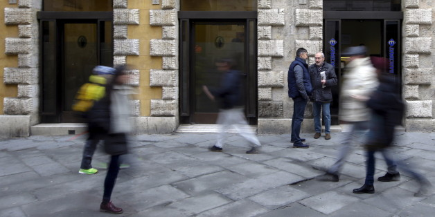 People walk in front of the Monte dei Paschi bank in Siena, central Italy, January 29, 2016. Merger talks between Italian cooperative lenders Banco Popolare and Banca Popolare di Milano (BPM) took a big step forward on Thursday when Rome backed a tie-up. The two banks are at an advanced stage in merger talks and a combination would create Italy's third biggest lender by assets, just ahead of Monte dei Paschi di Siena. If successful, it would likely be the first merger since a reform of large cooperative lenders last year to encourage consolidation and strengthen Italy's fragmented banking system and could pave the way for a parallel deal between UBI, which had courted BPM, and Monte dei Paschi di Siena. REUTERS/Max Rossi