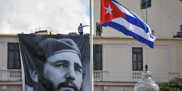 A Cuban flag flutters at half mast near a banner depicting Cuban revolutionary leader Fidel Castro, two days after his death, in Havana on November 27, 2016.Cuban revolutionary icon Fidel Castro died late November 25 in Havana, his brother, President Raul Castro, announced on national television. Castro's ashes will be buried in the historic southeastern city of Santiago on December 4 after a four-day procession through the country. / AFP / Yamil LAGE        (Photo credit should read YAMIL LAGE/