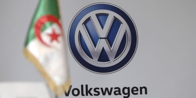 The Algerian national flag is seen in front of a German carmaker Volkswagen (VW) logo during a meeting to sign a protocol agreement for the construction of a plant in the industrial zone of Sidi Khettab, on November 27, 2016 in the capital Algiers. Volkswagen and Algerian group Sovac agreed to launch shortly a car assembly plant in Relizane, some 320km west of Algiers. / AFP / RYAD KRAMDI        (Photo credit should read RYAD KRAMDI/AFP/Getty Images)