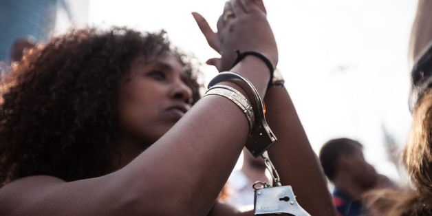 A demonstrator is wearing a handcuff, during a demonstration of Ethiopian Jews in Tel Aviv on May 3, 2015. A few thousands people marched through Tel Aviv in what was mostly a peaceful demonstration against police brutality directed against the Jewish Ethiopian community in Israel. During the early evening hours the demo turned violent as clashes broke between the protesters and the police, some 40 people were injured. (Photo by Omer Messinger/NurPhoto) (Photo by NurPhoto/NurPhoto via Getty Imag