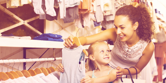 Positive young mother with daughter buying kids clothes in blue color in shop