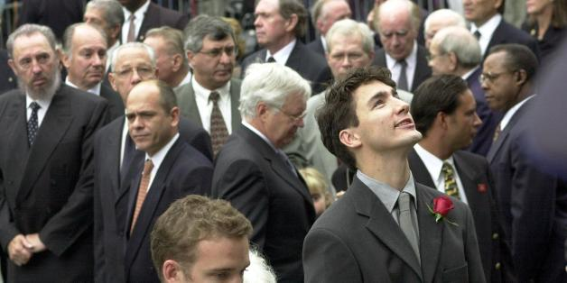 MONTREAL, CANADA - OCTOBER 3:  The son of former Canadian Prime Minister Pierre Trudeau, Justin (R),  looks up as he arrives in the company of his brother Sacha (lower center) at the state funeral for their father at the Notre Dame Basilica during Trudeau's state funeral 03 October 2000. Trudeau, who was considered to be one of Canada's most charismatic prime ministers, died of prostate cancer at age 80 at his home 28 September. Cuban President Fidel Castro can be seen at left.  (Photo credit should read PHIL CARPENTER/AFP/Getty Images)