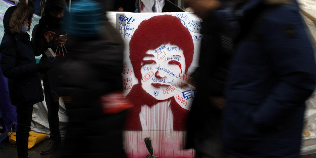SEOUL, SOUTH KOREA - NOVEMBER 26:  People gathered for a rally against South Korean President Park Geun-hye and pass by Park Geun-hye's portraits on November 26, 2016 in Seoul, South Korea.  Park has recorded worst ever polling figures for the country's presidency after her friend Choi Soon-sil was charged with corrupt influence over state affairs.  (Photo by Woohae Cho/Getty Images)