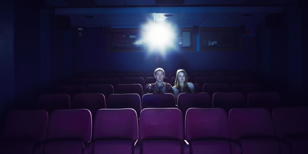 Couple watching a movie in an empty cinema