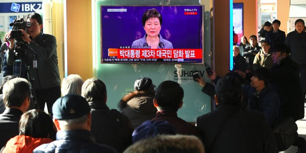 People watch a television news live showing South Korean President Park Geun-Hye making a speech, at a railway station in Seoul on November 29, 2016.South Korea's scandal-hit President Park Geun-Hye said on November 29 she was willing to leave office before the end of her official term early 2018 and would let parliament decide on her fate. / AFP / JUNG Yeon-Je        (Photo credit should read JUNG YEON-JE/AFP/Getty Images)