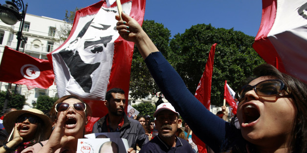 A demonstrator (L) holds a portrait of the late Tunisian opposition leader Chokri Belaid as others wave flags and a poster of slain opposition leader Mohamed Brahmi at an event commemorating the Feast of the Martyrs at Avenue Habib Bourguiba in Tunis, April 9, 2014. REUTERS/Anis Mili (TUNISIA - Tags: CIVIL UNREST POLITICS ANNIVERSARY)