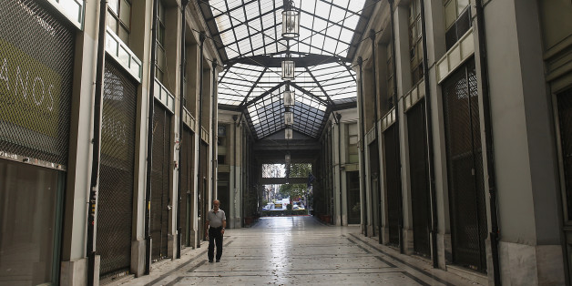 A pedestrian walks past closed and shuttered shops inside a shopping arcade in Athens, Greece, on Sunday, July 12, 2015. European finance chiefs said they were unlikely to strike a deal on the outlines of a third Greek bailout, threatening to delay the cash infusion Prime Minister Alexis Tsipras desperately needs. Photographer: Simon Dawson/Bloomberg via Getty Images