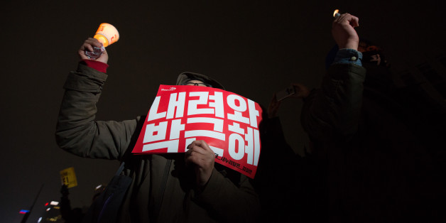 A protester holds a candle and a placard during a rally in Seoul, South Korea, on Saturday, Nov. 26, 2016. Hundreds of thousands of South Korean protesters marched to President Park Geun-hye's office, beating drums and chanting slogans, even as lawmakers considered impeaching her over an influence-peddling scandal. Photographer: SeongJoon Cho/Bloomberg via Getty Images