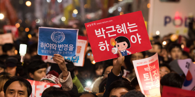 Protesters hold placards during a rally in Seoul, South Korea, on Saturday, Nov. 26, 2016. Hundreds of thousands of South Korean protesters marched to President Park Geun-hye's office, beating drums and chanting slogans, even as lawmakers considered impeaching her over an influence-peddling scandal. Photographer: SeongJoon Cho/Bloomberg via Getty Images