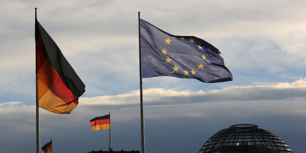 The German national flag flies beside a European Union (EU) flag outside the Chancellery in Berlin, Germany, on Friday, Nov. 18, 2016. Germany's Chancellor Merkel said she's ready to work with U.S. President-elect Donald Trump and won praise for her leadership from U.S. President Barack Obama, who suggested Germans would do well to re-elect her next year. Photographer: Krisztian Bocsi/Bloomberg via Getty Images