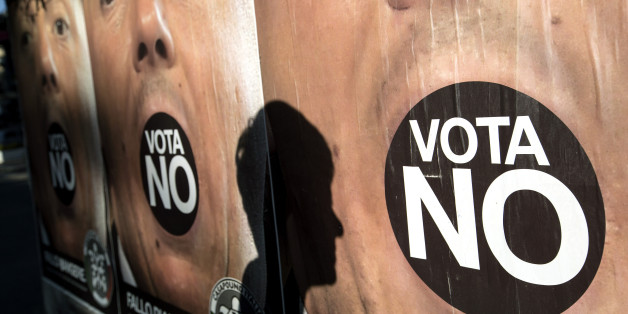 A pedestrian's shadow is cast on an advertising board displaying posters for the 'No' campaign ahead of the referendum on constitutional reform, in Rome, Italy, on Saturday, Dec. 3, 2016. On Dec. 4, Italians will vote on constitutional changes proposed by Prime Minister Matteo Renzi to limit the power of the Senate, the upper house of parliament. Photographer: Alessia Pierdomenico/Bloomberg via Getty Images