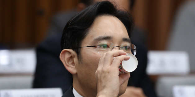 Jay Y. Lee, co-vice chairman of Samsung Electronics Co., takes a drink during a parliamentary hearing at the National Assembly in Seoul, South Korea, on Tuesday, Dec. 6, 2016. Lee, the de-facto head of Samsung, became the focus of the hearing of South Korea's top tycoons in connection with a widening influence-peddling scandal that may cost the country's president her job. Photographer: SeongJoon Cho/Bloomberg via Getty Images