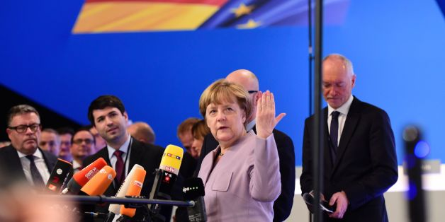 German Chancellor Angela Merkel speaks with journalists as she visits the venue of their Christian Democratic Union (CDU) party's congress in Essen, western Germany, on December 5, 2016. 