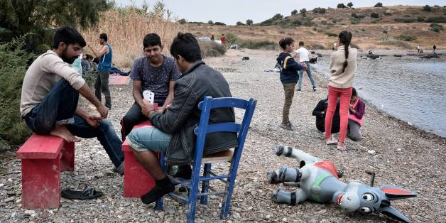 Refugees play cards on the beach at an unofficial migrant camp, run by activists on the island of Lesbos  on September 22, 2016.  / AFP / LOUISA GOULIAMAKI        (Photo credit should read LOUISA GOULIAMAKI/AFP/Getty Images)