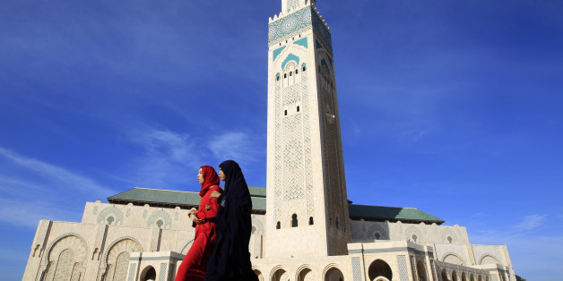 Moroccan women walk past the Hassan II mosque in Casablanca February 24, 2011. The minaret of the mosque is the highest in the world, standing at 210 metres (689 feet).    REUTERS/Pascal Rossignol (MOROCCO - Tags: RELIGION IMAGES OF THE DAY)