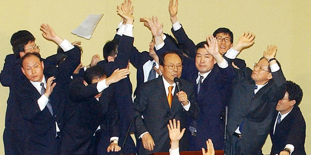 SEOUL, REPUBLIC OF KOREA:  South Korea's parliamentary security guards surround Speaker Park Kwan-Yong (C) as he announces the National Assembly's vote results of 193 votes to two to impeach President Roh Moo-Hyun, in Seoul 12 March 2004.  Roh was suspended from office after opposition lawmakers passed an historic impeachment vote, leaving the country in political chaos.   AFP PHOTO  (Photo credit should read STR/AFP/Getty Images)