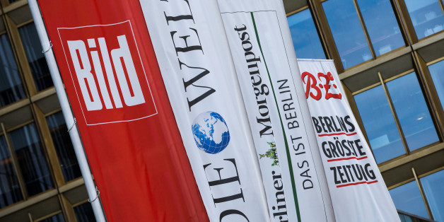 Flags with the logos of the main newspapers of German publisher Axel Springer fly outside its headquarters in Berlin August 7, 2013.    REUTERS/Thomas Peter/File Photo         GLOBAL BUSINESS WEEK AHEAD PACKAGE - SEARCH 'BUSINESS WEEK AHEAD MAY 9'  FOR ALL IMAGES