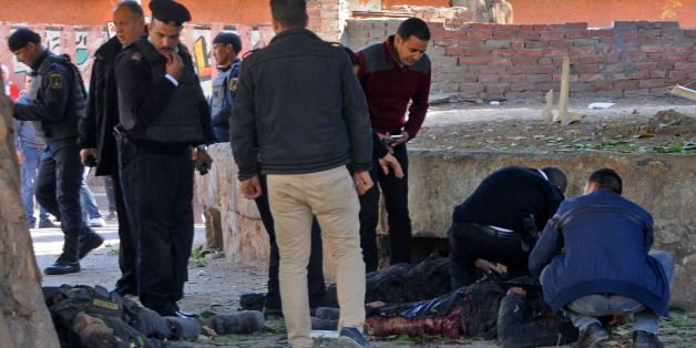EDITORS NOTE: Graphic content / Egyptians check bodies at the site of a bomb attack next to a police checkpoint in the western Talibiya district of the capital Cairo on December 9, 2016.  / AFP / STRINGER        (Photo credit should read STRINGER/AFP/Getty Images)