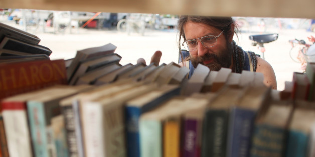 """Dario Clocchiatti looks for a book at one of the temporary libraries on the """"Playa"""" as approximately 70,000 people from all over the world gather for the 30th annual Burning Man arts and music festival in the Black Rock Desert of Nevada, U.S. September 3, 2016. REUTERS/Jim Urquhart FOR USE WITH BURNING MAN RELATED REPORTING ONLY. FOR EDITORIAL USE ONLY. NOT FOR SALE FOR MARKETING OR ADVERTISING CAMPAIGNS. NO THIRD PARTY SALES. NOT FOR USE BY REUTERS THIRD PARTY DISTRIBUTORS"""